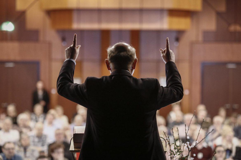 Businessfotografie: Präsentation vor der Kamera beim Fotoshooting, Mann von hinten mit den Händen nach oben vor einem Publikum